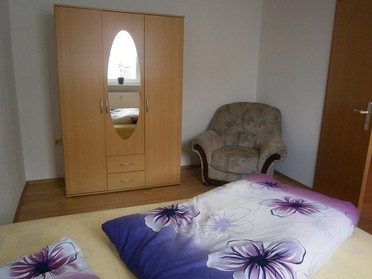 Die Ferienwohnug 1 mit einem der beiden Schlafzimmer in der Rückertstraße 3 in 99734 Nordhausen mit bett, Kleideschrank mit Spiegel in der Pension in Nordhausen