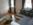 Wohnzimmer der Ferienwohnung 2 in der Rückertstraße 3 in 99734 Nordhausen mit goldbedruckten Gardinen, gemütlicher großer Couch, Tisch und Flachbildfernseher